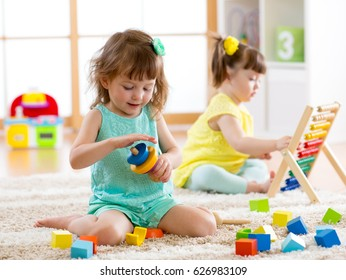 Children toddlers girls play logical toy learning shapes, arithmetic and colors at home or nursery.