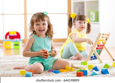 Children toddlers girls play logical toy learning shapes, arithmetic and colors at home, kindergarten or nursery