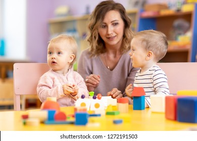 Children toddlers with kindergarten teacher is playing with montessori material. Learning through experience concept, gross and fine motor skills.