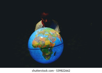 Children touch Globe model.He was looking at a globe with the intention ,black background