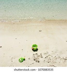 Children toy on the sea sand beach. High angle view.
