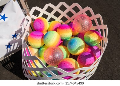Children Toy Rainbow Colored Balls in a White Basket.