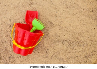 Children toys in a sandbox bucket scoop rake flat top view with a copy space