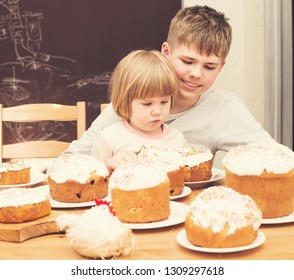 Children with traditional Easter homemade cakes and colored eggs. Teen boy and little girl sitting at the table full of traditional Easter cakes. Easter holiday concept.