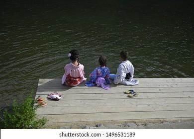 Children in traditional Japanese clothes splashing water by feet at Katsura River in Arashiyama, Kyoto, Japan