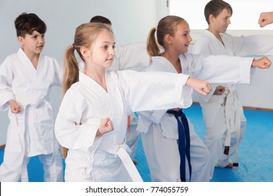 Children training a new moves with coach during karate class