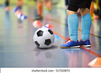 Children training soccer/ futsal indoor gym. Young boy with soccer ball training indoor football. Little player in light blue sports socks