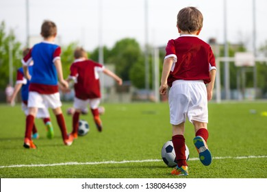 Children Training Soccer on Field. Young Kids Boys kicking Soccer Football Balls on Grass Pitch. Kids in Sportswear Practice Soccer Skills