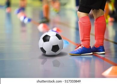 Children training soccer/futsal indoor gym. Young boy with soccer ball training indoor football. Little player in light red sports socks