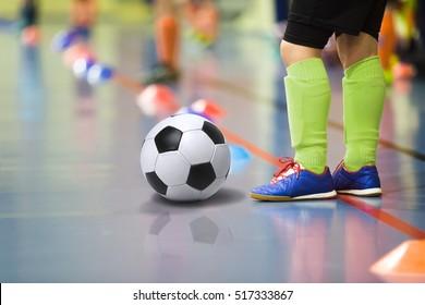 Children training soccer/futsal indoor gym. Young boy with soccer ball training indoor football. Little player in light green sports socks