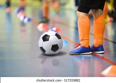 Children training soccer/futsal indoor gym. Young boy with soccer ball training indoor football. Little player in light orange sports socks