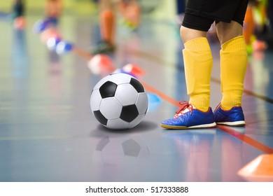Children training soccer/futsal indoor gym. Young boy with soccer ball training indoor football. Little player in yellow sports socks