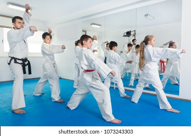Children trying new martial moves in a practice during karate class in gym