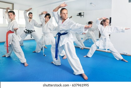Children trying new martial moves in practice during karate class in a gym