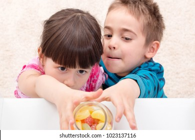Children trying to take candy put aside