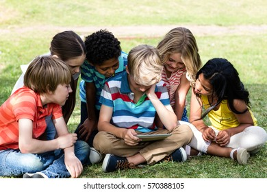 Children using digital tablet in the park