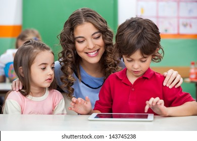 Children using digital tablet with teacher at classroom desk