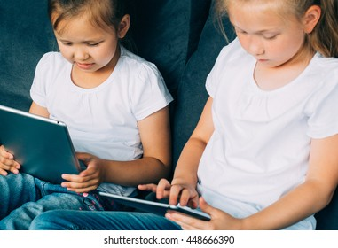Children using tablet. Two girls sisters friends with tablet home together surfing internet playing games online