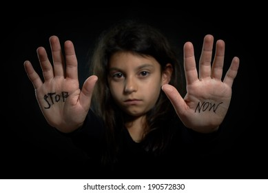 Children violence. Stop now are write on extended girl's hands.
