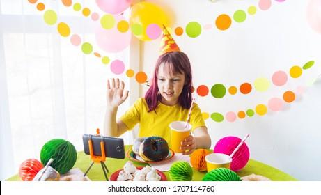 Kinder virtuelle Geburtstagsfeier mit Kuchen online zusammen mit ihrer Freundin in Videokonferenz. Mit digitalem Telefon für ein Online-Meeting. Mädchen feiert Geburtstag online in Quarantänezeit