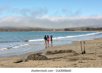 Children wading in the waves at a beach. Doran Park, Sonoma County, California, USA