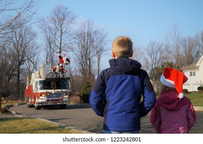 Children waiting for Santa on a firetruck. A young boy and girl look on as a firetruck approaches with Santa.