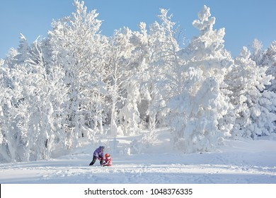 Children walk near the snowy forest