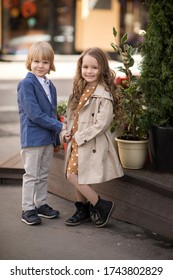 Children walk in the spring city. A boy and a girl stand nearby and hold hands. Image with selective focus.