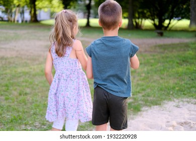 children walk in a summer park, a boy in shorts and a girl of 6-7 years old in dress are walking together on playground, holding hands, concept of active lifestyle, children's friendship