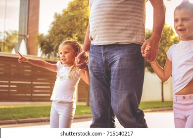 Children walking with their  grandfather holding hands. Little girl showing something with finger.