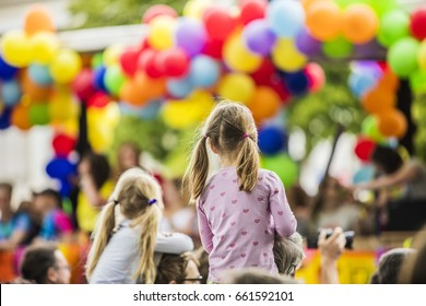 children watching colorful rainbow parade