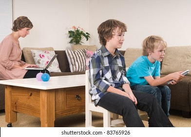 Children are watching tv while mother is working in the background
