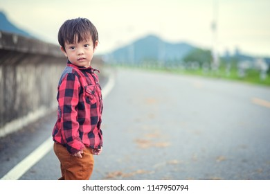 A Children wear Jacket to traval and stand in the park.
