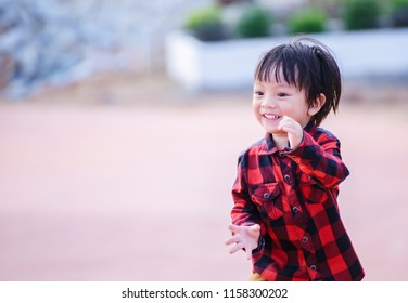 A Children wear Jacket to traval and stand in the park. Children smiling.