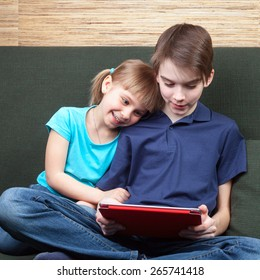 Children wearing casual clothes playing or watching a movie on a touch pad at home sitting on a green sofa. Boy and girl are half-siblings. Brother is holding tablet with red cover.