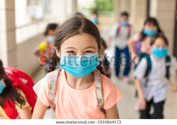 children wearing  face medical mask back to school after covid-19 quarantine