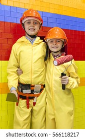 children wearing hard hats and yellow overalls are holding construction tools