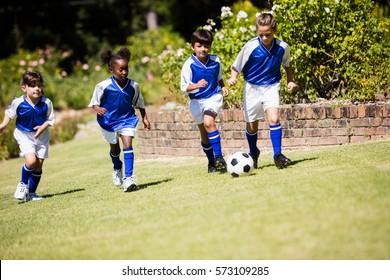 Children wearing soccer uniform playing a match in a park