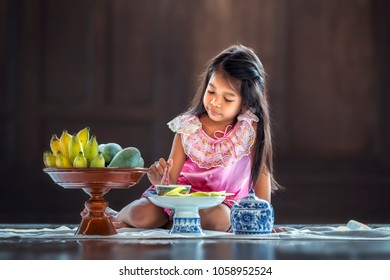 Children wearing traditional Thai dress eating fruit