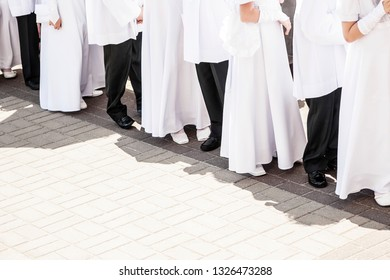 Children in white tunics of first communion waiting for ceremony.