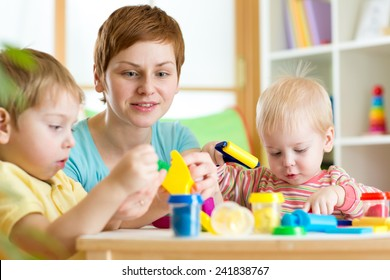 children and woman with colorful plasticine at home or play school