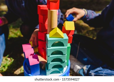 Children with wooden building blocks playing helped by an adult outdoors.