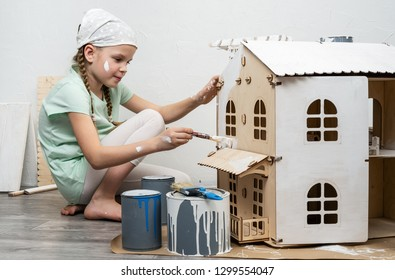 Children at work: The girl neatly paints the facade of the doll house with a small tassel in white.
