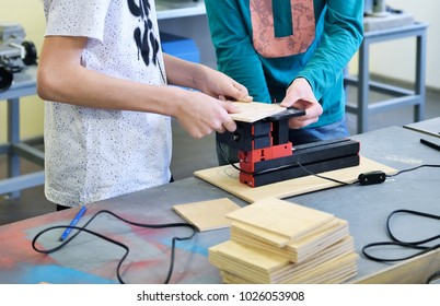 Children work in the training center on wood processing machines. Education in Fablab. Innovative technologies of manufacturing.