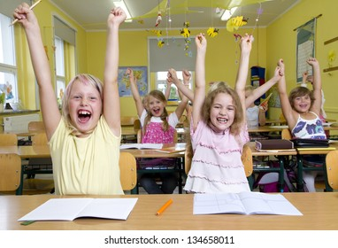 Children in a yellow classroom. They all raises up the hands.