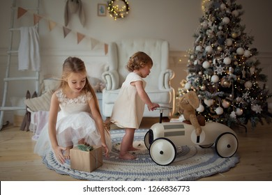 Children-girls in elegant dresses playing with toys at the Christmas tree. New year and Christmas.