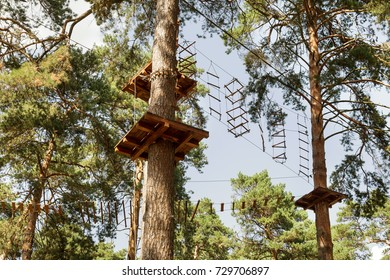 Children's Adventure Park bridges, ropes and stairs designed for beginners in woods among tall pine trees. Adventure climbing on high wired park. Course of high ropes in forest.
