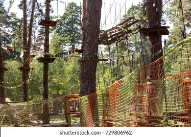 Children's Adventure Park bridges, ropes and stairs designed for beginners in woods among tall pine trees. Adventure climbing on high wired park. Course of high ropes in forest. Activity