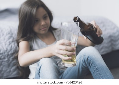 Children's alcoholism. A little dark-haired girl sits leaning on the bed and pours herself a beer from the bottle into the glass