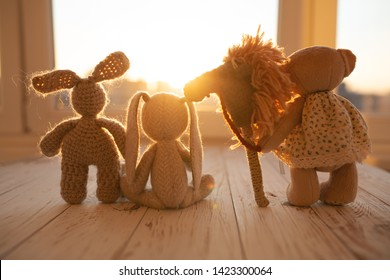 Children's animal stuffed toys bunny and teddy family on wooden floor in kids room.